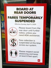 A sign on the door of an RTD bus in Denver tells riders that fares have been suspended during the coronavirus outbreak.