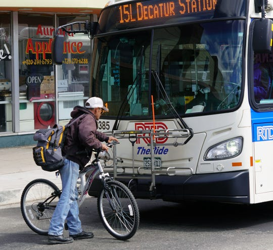 A passenger loads his bike onto an RTD bus in Denver before boarding during the coronavirus outbreak.