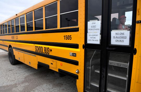 Kathy Higgins sits in and idling school bus being used as a wifi hotspot in a parking lot on Kirkwood Street between North 2nd and North Third streets Tuesday. The Abilene Independent School District has outfitted a handful of buses which are stationed at several sites around the city for students to utilize.
