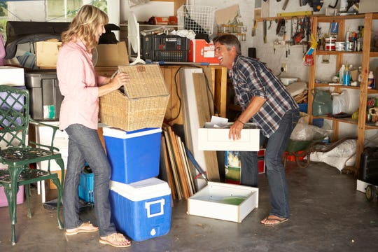 Couple Clearing Garage For Yard Sale Laughing