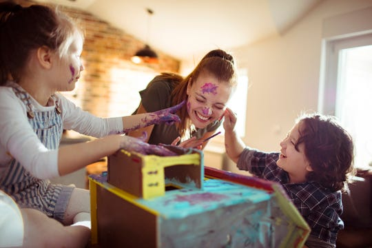 A mother colors a doll house with her young kids