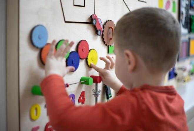 A young boy plays o a busy board.