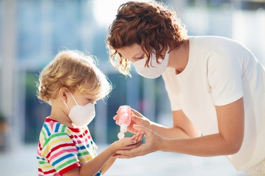 A puts hand sanitizer on her child while wearing facemasks during the coronavirus outbreak.