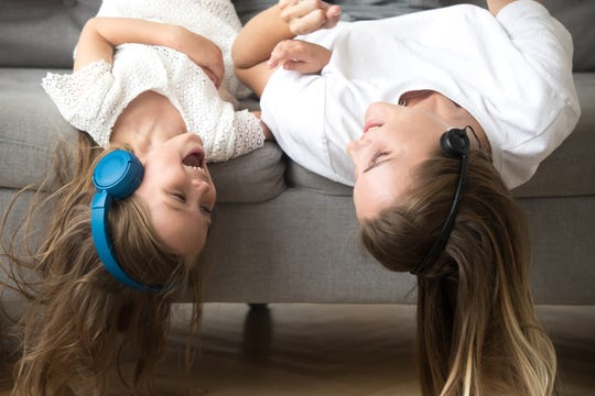 A mom and child hang upside-down while listening to music.