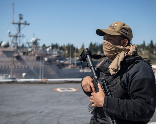 Airman Arlon Jones from Columbia, S.C., stands security watch on the flight deck aboard the aircraft carrier USS Nimitz while the carrier is in Bremerton. He wears a T-shirt over his mouth as a cloth mask.
