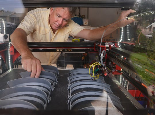 Cape Canaveral freelance illustrator Don Foley checks out COVID-19 face shields inside his Modix Big-60 3D printer at his shop.