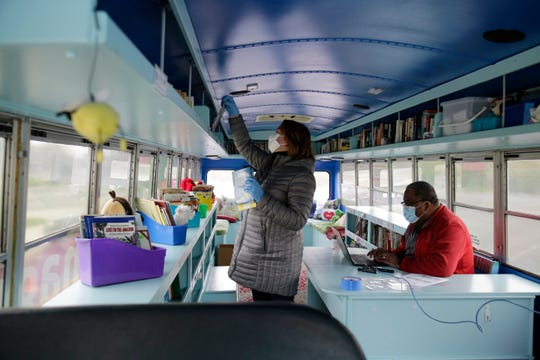 Tricia Roddy, communications director for Princeton City Schools, picks out age-appropriate books for students while technology director Chris Lockhart sets up a mobile network inside the Mobile Book Center while it's parked outside Heritage Hill Elementary in Springdale, Ohio, on Tuesday, April 14, 2020.
