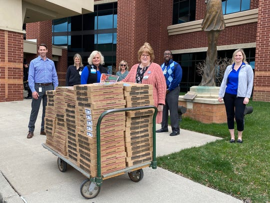 Atrium Medical Center staff and representatives from Ohio Living Home Health/Ohio Living Mt. Pleasant after the aging services organization donated more than 100 pizzas to feed hospital employees.