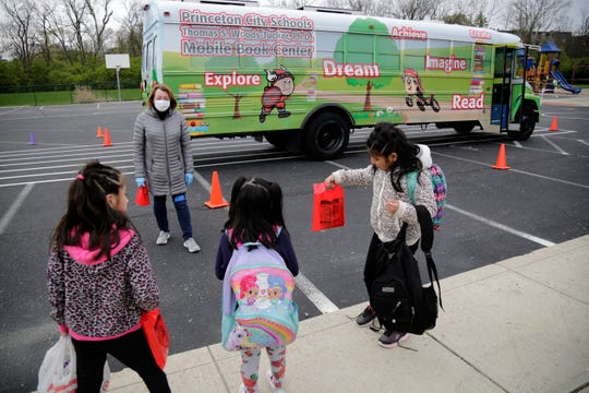 Tricia Roddy, communications director for Princeton City Schools, picks out age-appropriate books for students from the Mobile Book Center while it's parked outside Heritage Hill Elementary in Springdale, Ohio, on Tuesday, April 14, 2020. The Book Center is currently donating books outright as it suspends return policies amid the COVID-19 pandemic.