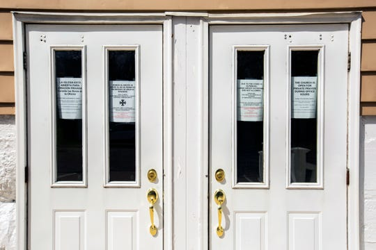 Signs in Spanish and English are seen on doors at St. Joseph Church on updates related to COVID-19 in Columbus Junction.