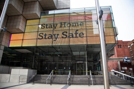 "The electronic sign outside of the TCF Center in Detroit cautions ""Stay Home Stay Safe"" as entrances to the center are closed off Tuesday, April, 14, 2020."