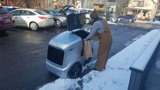 The Refraction AI robot features UV lights inside that are capable of killing viruses. A Miss Kim staffer loads food for delivery into the autonomous bot.
