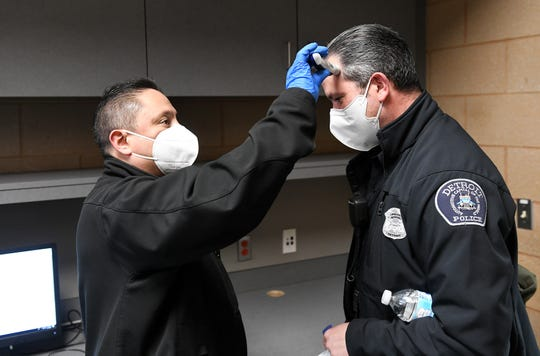 From left, Detroit police Sgt. Manny Gutierrez takes the temperature of officer J. Gorgon at the end of Gorgon's shift at the Detroit police department 4th Precinct in Detroit on April 14, 2020.  The police department has implemented various safety measures due to the coronavirus, such as taking the temperatures of officers arriving for duty and also at the end of their shift.