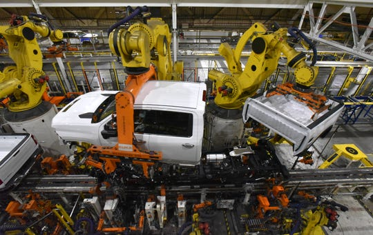 Robots attach cabs and boxes to truck chassis. But for final assembly, most auto plants are crowded with robots, not humans.