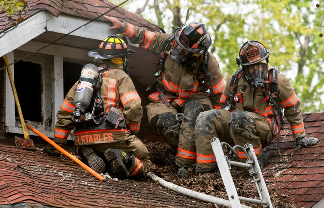 Evansville Fire Firefighters exit an attic window as they work to extinguish a fire in a home at 305 S Boeke Road Tuesday morning, April 14, 2020. Evansville Fire Department investigators believe the fire appeared to have started on the outside wall of the residence before spreading to the attic.