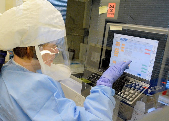 Elaine Ulgenes of the DPHHS State Public Health Laboratory enters information into a RNA extractor instrument as part of the COVID-19 testing process. This instrument isolates the RNA from COVID-19 samples that is later tested for the virus.