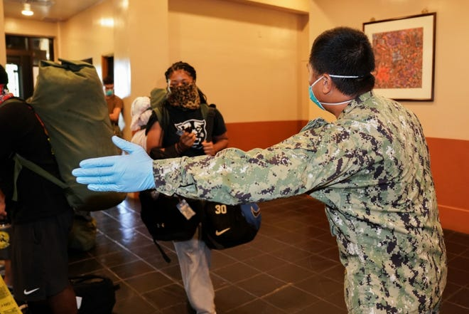 A sailor assigned to Commander, Submarine Squadron Fifteen directs sailors assigned to the aircraft carrier USS Theodore Roosevelt (CVN 71) who have tested negative for COVID-19 and are asymptomatic into the check-in line for room assignment at a Government of Guam and military-approved commercial lodging. Theodore Roosevelt sailors were moved to local hotels in an effort to implement an aggressive mitigation strategy to minimize the spread of COVID-19 and protect the health of the sailors. Sailors remain in quarantine in their assigned lodging for at least 14 days, in accordance with DoD directive and the governor's executive order.