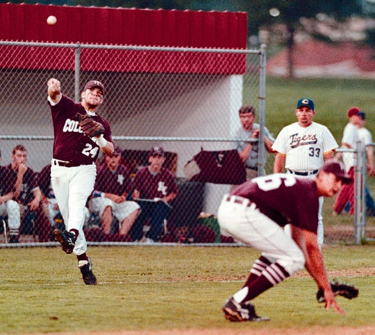 Henderson County third baseman Neil Sellers (24) launches the ball for an out at first as pitcher Seth Stanley (26) ducks during the 1998 Second Region Tournament against Caldwell County at Christian County High School.
