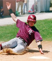 Henderson County'sTodd Satterfield slides into home to score the last of his team's seven runs during their game against Marion, Illinois, on May 10, 1997. Satterfield scored easily from third on a sacrifice fly.