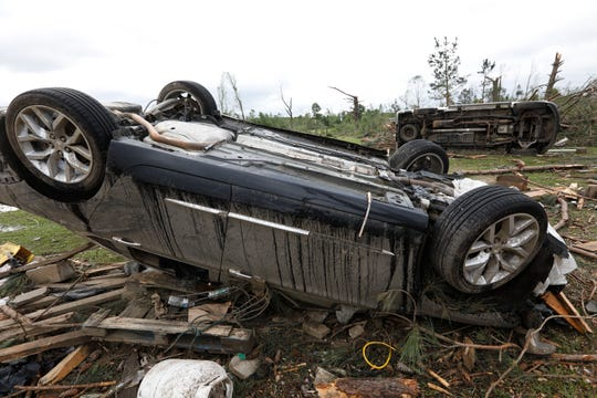 Overturned sedans rest about 100 feet from a bar and grill in this Bassfield, Miss., neighborhood, Monday, April 13, 2020. The community was one of many in Mississippi swept by a series of tornadoes, Sunday afternoon and evening.