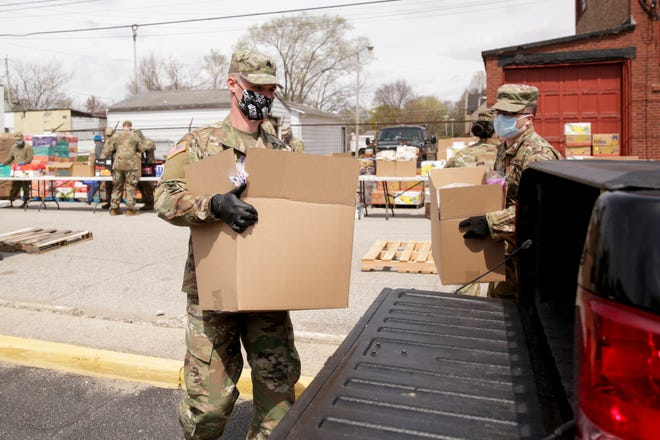 Members of the Indiana National Guard load cars with food items at a drive-thru pantry for Food Finders Food Bank outside of Linwood Elementary School, Tuesday, April 14, 2020 in Lafayette.