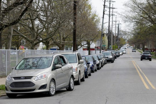 Cars line up around Linwood Elementary School before the start of the drive-thru pantry for the Food Finders Food Bank, Tuesday, April 14, 2020 in Lafayette.