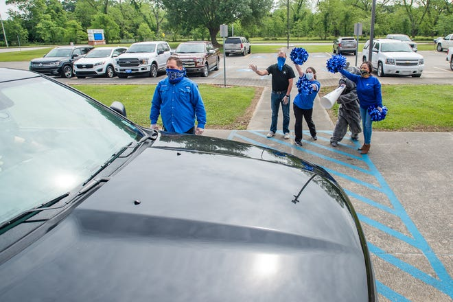 Faculty members cheer as students at David Thibodaux STEM  Magnet Academy Students pick up graduation supplies in drive thru at the school. Tuesday, April 14, 2020.