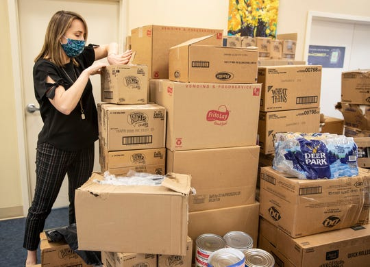 Kate Brackett, Vice President of Strategic Initiative for the Family Scholar House opened boxes of food from Kentucky Harvest. The food will will be distributed to the 247 families the agency houses. April 14, 2020