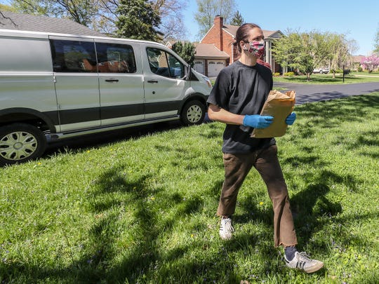 Evan Strange, who works for Carmichael's Bookstore, makes a delivery of books to a home on Thursday, April 9, 2020.  Strange, who normally splits his time behind the counter and behind the wheel, has made the store's delivery van his new office as online orders have soared.