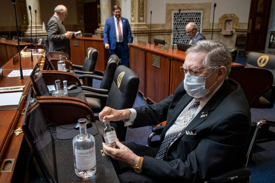Senator C.B. Embry, Jr. examines the hand sanitizer made by local distilleries during the last two days of the Senate session at the Capitol building in Frankfort. April 14, 2020