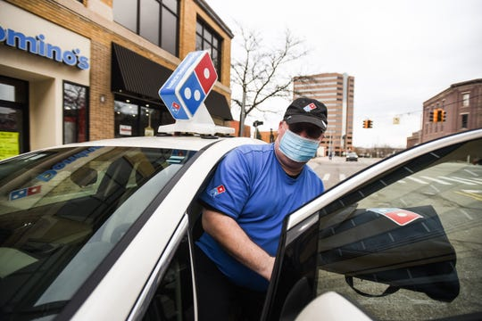 """""""Everything we do is about safety,"""" Domino's Pizza driver Craig Bailey said on April 14, 2020 while heading out for a delivery from the downtown Lansing location.  """"We wear masks, gloves, maintain social distance."""""""
