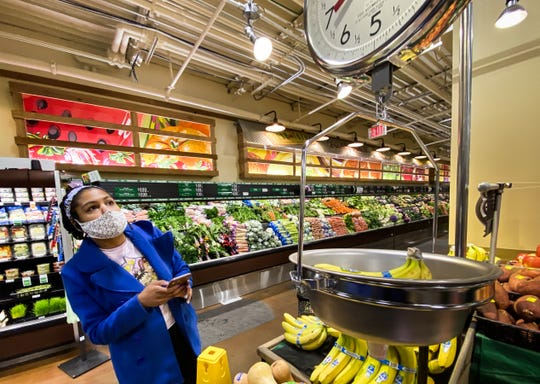Ti'Air Riggins of Lansing weighs bananas for an Instacart client at Fresh Thyme in East Lansing on Monday, April 13, 2020.  She says a few customers during the COVID-19 pandemic have lured her with promises of big tips but then modified or canceled the tips after delivery.