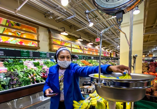 Ti'Air Riggins of Lansing weighs bananas for an Instacart client at Fresh Thyme in East Lansing on Monday, April 13, 2020.