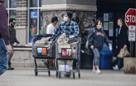 A shopper wears a mask as he exits the Oconomowoc Pick 'n Save on Sunday, April 12, 2020. Pick 'n Save and Metro Market grocery stores have implemented exclusive shopping hours for seniors 60 and older between 6 a.m. to 8 a.m. daily. They have also limited the number of shoppers allowed in the stores.