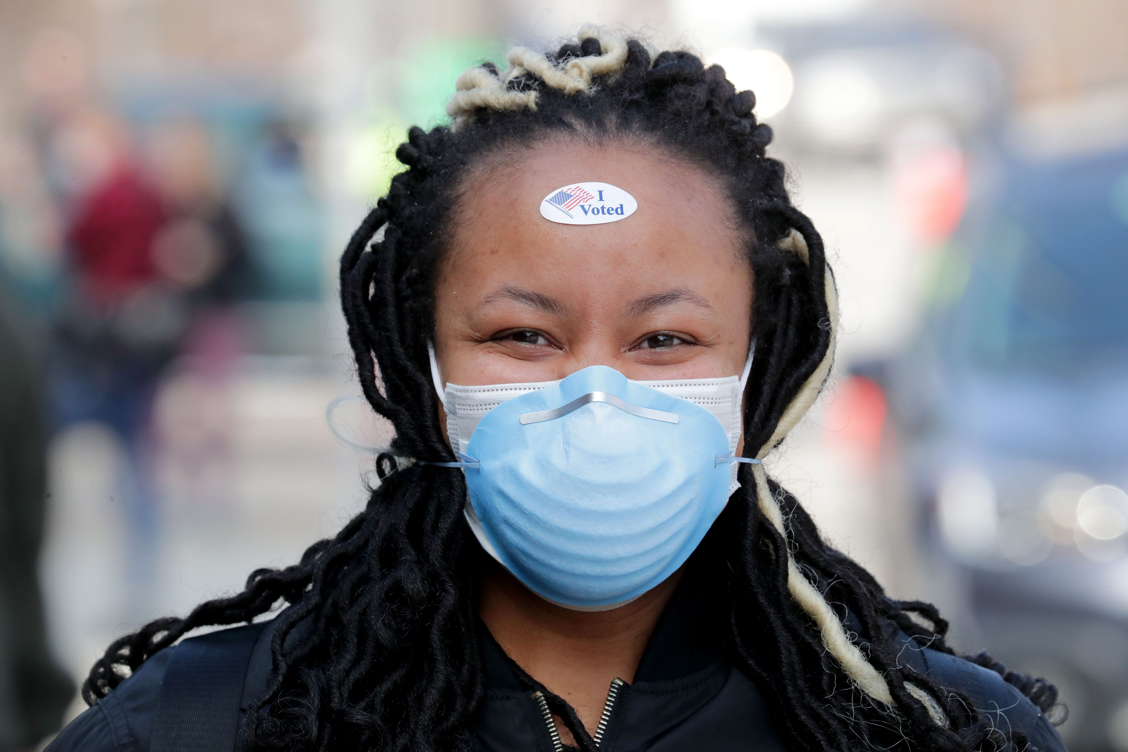 Sierra Woodard smiles through her face mask after waiting 2 hours and 22 minutes to vote at Riverside High School in Milwaukee April 7