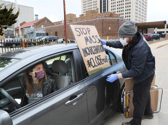 Advocates from the Forum for Understanding Prisons staged a car protest April 9 driving around the Milwaukee Secure Detention Facility at 1015 North 9th Street in Milwaukee, demanding prisoners be released to decrease their risk of getting coronavirus. Ben Turk of Milwaukee, puts a protest sign on Eliana Winter Light of Milwaukee, car.