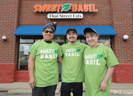 Sweet Basil restaurant owner Ken Sithy, center, stands with his father, Lamkeo Xayasone, head chef, and his mother, Vanna Praseutsack, sous chef, outside the restaurant at 6509 S. 27th St. in Franklin. The family-owned Thai-Lao restaurant had its grand opening on Friday and  sold out of all food for the weekend by 6:30 p.m. Sweet Basil reopened Tuesday.