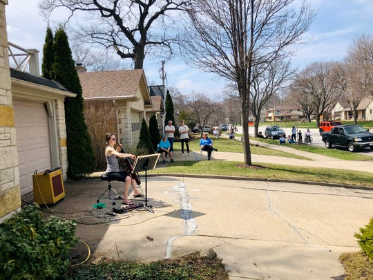 Madeleine Kabat, a cellist for the Milwaukee Symphony Orchestra, played a social distancing concert with her husband, Peter Thomas, for their neighbors in the Swan Park neighborhood April 7.
