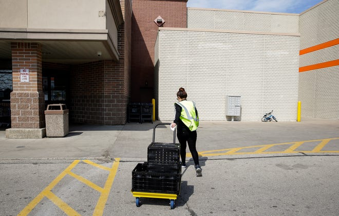 Maria Gonzalez drags a cart back to a storage room after loading groceries for customer's pickup order April 7 in Milwaukee.