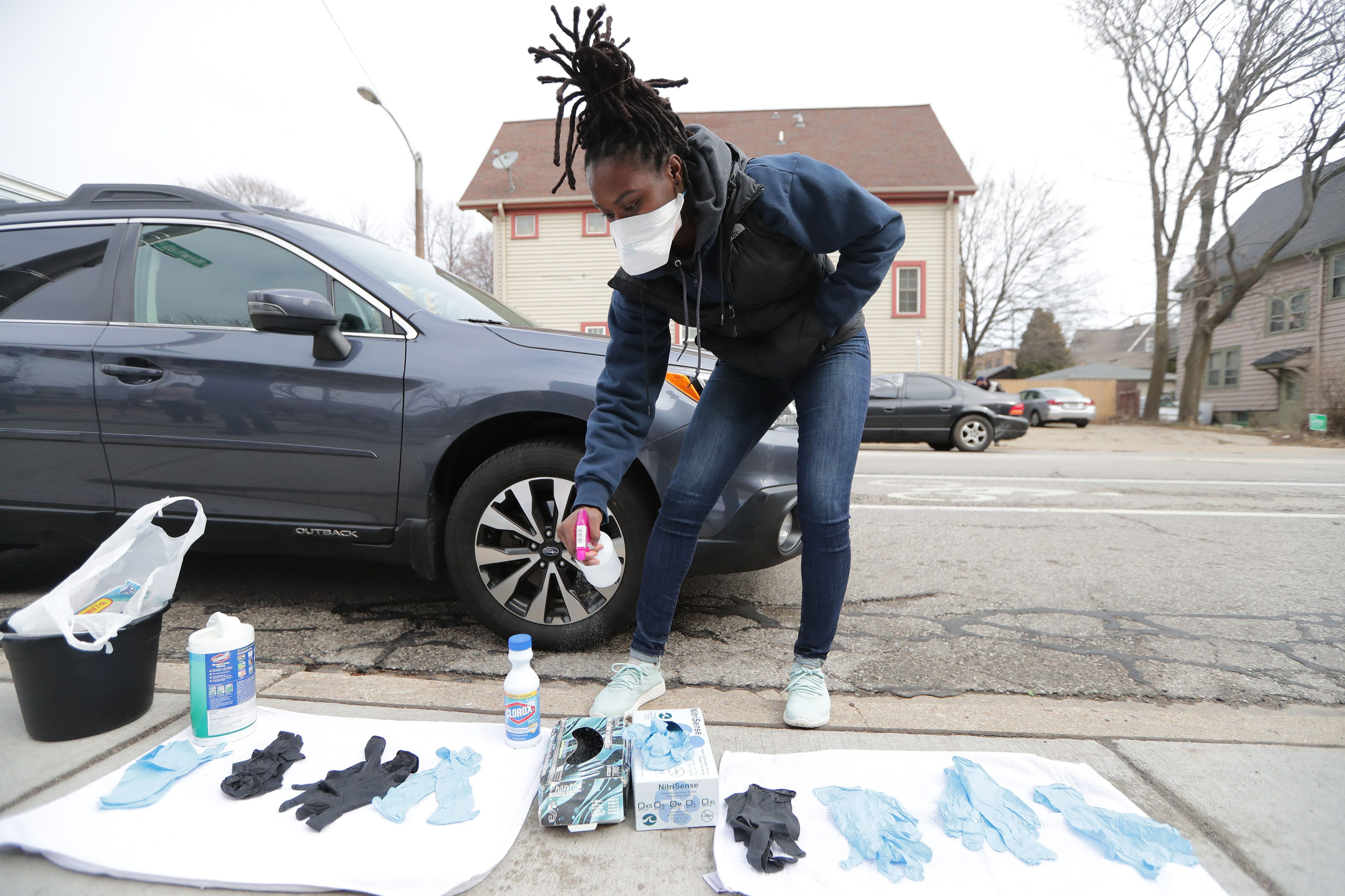 """""""I went to bed last night and my heart was sinking just thinking about the polling place situation going from 180 to 5,"""" said Breana Stephens, of Milwaukee, who brought out rubber gloves to pass out to voters at Riverside High School, April 7."""
