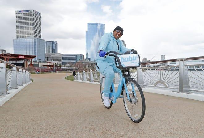 C. Burke, of Milwaukee, rides a Bublr bike through Lakeshore State Park in Milwaukee on April 9.