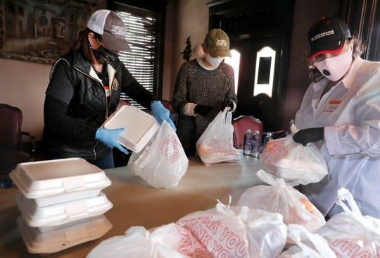 Lynn DeGroff, left, Jamie McKay, center, right, and Lorie Witt, right, place meals in bags that were distributed through Milano Central Kitchen at Milano II in downtown Murfreesboro, on Tuesday, April 14, 2020, in Murfreesboro.