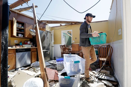 Matthew Alexander carries items through the kitchen of the damaged home of his in-laws as he helps to salvage items Tuesday, April 14, 2020, in Chattanooga, Tenn. Tornadoes went through the area two days before.