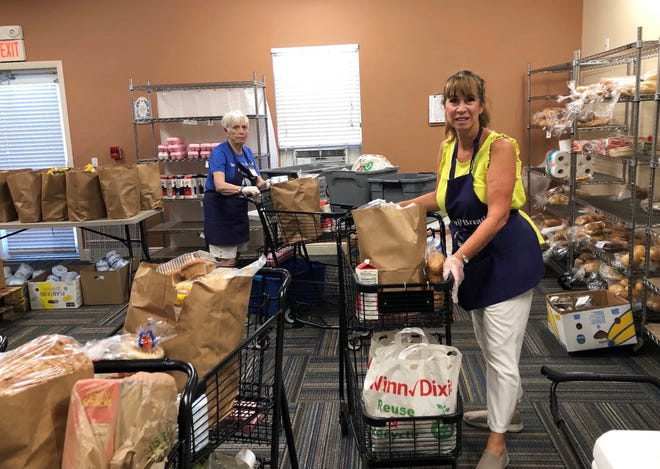 Volunteers prepare shopping carts with food items for distribution.