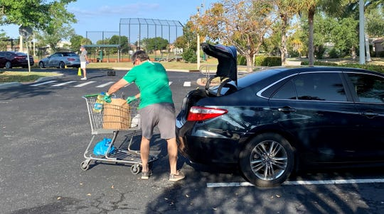 At a recent Saturday drive-in food distribution, volunteer Ray Kane loads groceries, while observing CDC guidelines for social distancing.