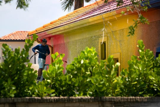 Work to repaint a rainbow-colored splattered home located at Regalo Circle in North Naples began on Tuesday, April 14, 2020.