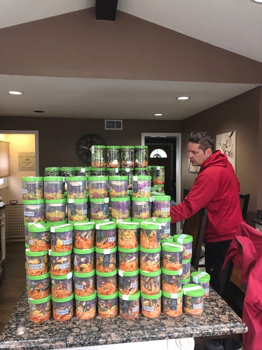 Kelly Carroll counts a bounty of fresh organic salads to be delivered to needy families struggling to make ends meet during the coronavirus emergency.