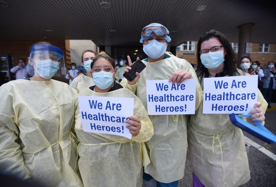 """Hospital workers hold up their signs as Paramus First Responders hold an appreciation """"clap out"""" at Bergen New Bridge Medical Center in Paramus, NJ on 04/14/20."""