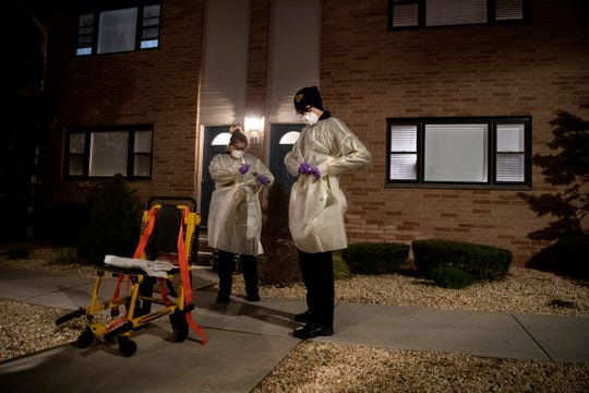 Hackensack Volunteer Ambulance Corps members (center) Silvio Zapata and Johanna Stange put on protective equipment before responding to call at 9:21 p.m. on Tuesday, April 7. 2020.