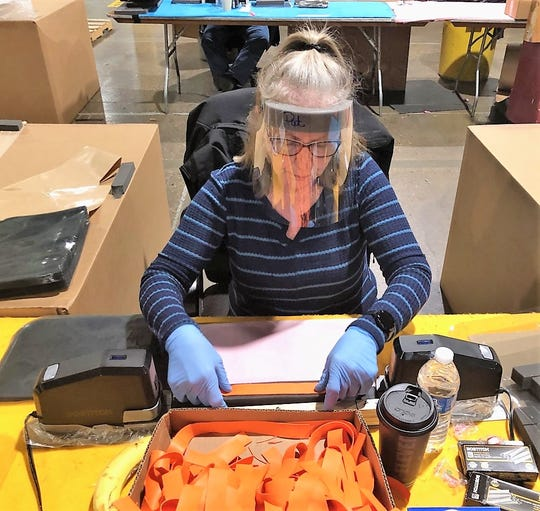Troy Design and Manufacturing employee Pat Tucker works on assembling a face shield.